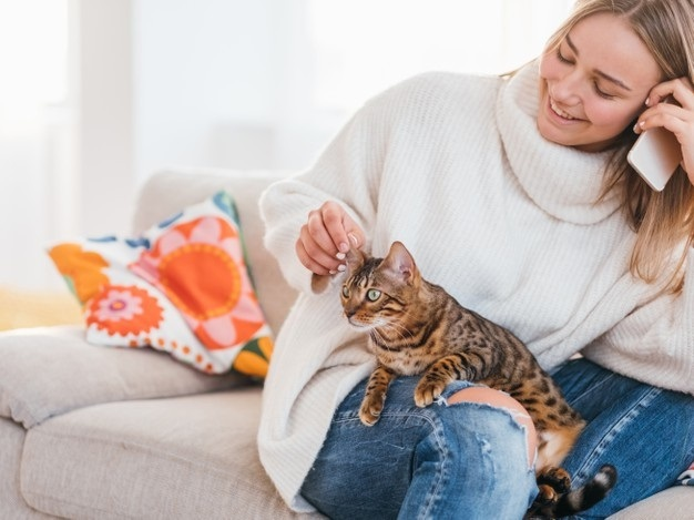 cosy-home-atmosphere-family-pet-girl-stroking-her-bengal-cat-while-talking-phone_201836-5507